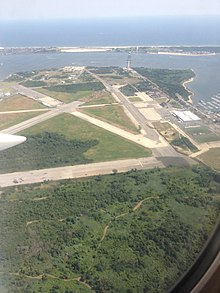 Aerial view of runways amid a grassy field, with a bay in the background