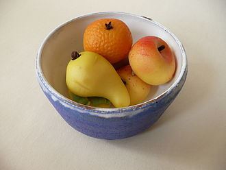 Marzipan - A bowl containing several fruit-shaped marzipan pieces