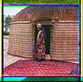 Full-length profile portrait of a woman, possibly Turkman or Kirgiz, standing on a carpet at the entrance to a yurt, dressed in traditional clothing and jewelry LOC 9628194209.jpg