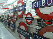 A collection of London Underground roundels from many stations displayed on a wire mesh screen