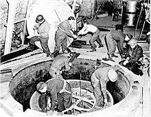 Soldaten und Arbeiter, einige mit Stahlhelm, klettern über ein riesiges Mannloch.
