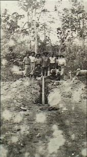 Soldiers digging up a long pipe like object that has been planted in the middle of a road.
