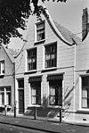foto van Huis met gepleisterde tuitgevel, zesruits schuifvensters, stoeppalen onderling verbonden door ijzeren stangen en met de gevel door krulijzers