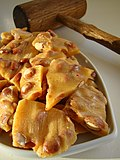 Golden peanut brittle cracked on a serving dish.jpg