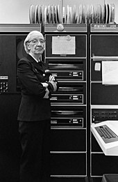 A black and white image of a white woman wearing glasses and a US Naval uniform standing in front of a bank of 1970's computer equipment