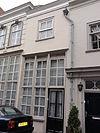 foto van Simpel huisje met grijsgepleisterde lijstgevel waarin een bovenvenster en winkelpui