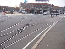A photo of taxpayer buildings in Boston, with streetcar tracks in the foreground.