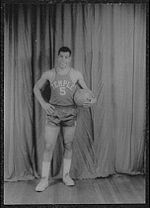 "A man, wearing a jersey with a word ""TEMPLE"" and the number ""5"" written in the front, is holding a basketball while posing for a photo."