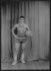 "A man, wearing a jersey with a word ""TEMPLE"" and the number ""5"" written in the front, is holding a basketball while posing for a photo"