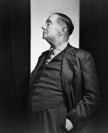 Nigra kaj blanka foto de H. G. Wells staranta kaj portanta vestokompleton