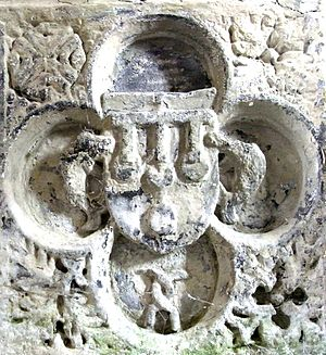 Manor of Molland - Fragment from a demolished Gothic chest tomb in Molland Church, showing within a quatrefoil the arms of Courtenay of Molland supported by two dolphins, a heraldic badge of Courtenay of Powderham, and showing beneath two interlaced Hungerford sickles