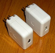 Two iPod wall chargers, with FireWire (left) and USB (right) connectors, which allow iPods to charge without a computer.