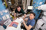 ISS-59 Nick Hague and Christina Koch work on EMUs inside the Quest airlock.jpg