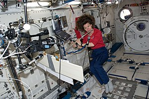 Women in space - Female astronaut Catherine Coleman playing a flute aboard ISS, 2011