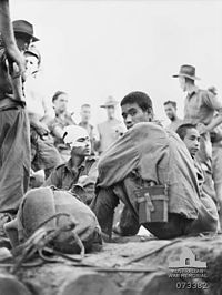 Japanese prisoners sitting, watched over by several Australians