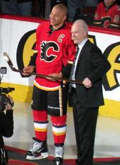 Um homem com uniforme completo de hóquei e outro homem de terno escuro seguram um taco de hóquei de ouro juntos enquanto olham para um fotógrafo invisível.