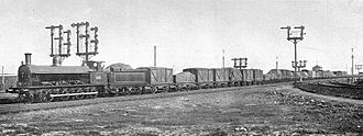 Rail freight in Great Britain - A goods train hauled by a LNWR Class C locomotive, passing through Crewe in 1907.