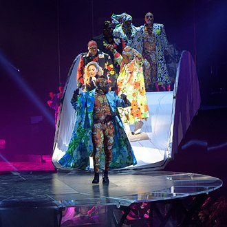 """Applause (Lady Gaga song) - Gaga and her dancers performing """"Applause"""" in flower-patterned outfits at the Joanne World Tour, in 2017"""