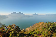View across hills to a broad lake bathed in a light mist. The mountainous lake shore curves from the left foreground backwards and to the right, with several volcanoes rising from the far shore, framed by a clear blue sky above.