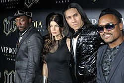 Two black men, a white man and a white woman standing in a line all wearing black clothing.