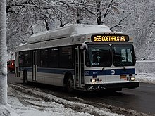 A Q65 bus as seen during a snowy day. The sign at the front of the bus signifies that it will short-turn at Goethals Avenue, rather than running the full route.