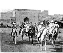 A photograph of General Mangin entering Marrakesh through a large gate at the head of a column of French horsemen