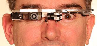 "EyeTap - EyeTap inventor Steve Mann wearing a metal frame Laser EyeTap (computer-controlled laser light source run from ""GlassEye"" camera)"