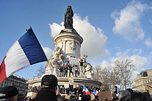Place de la République statue column with large French flag