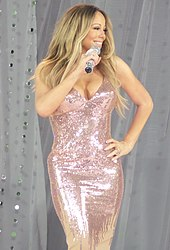 With chest length blond hair, a woman wearing a shimmering metallic dress holds a microphone and smiles.