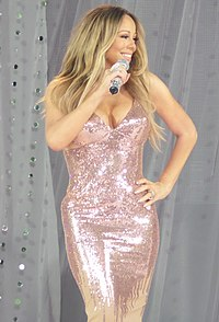 With long blonde hair, a woman smiles and holds a microphone, wearing a metallic dress.