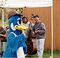 Mascot in the shape of duck dancing while musicians playing on instruments.jpg