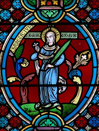Julia of Corsica - Sancta Julia from a stained glass window in Meaux Cathedral. She holds the Palm of martyrdom, a small crucifix and stands before a larger crucifix, the symbol of her crucifixion.