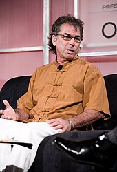 A man in an orange=colored shirt and white pants, sitting; he is wearing eyeglasses along with a microphone on his collar