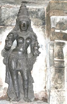 A stone carving of a standing woman with a pot in her left hand and lotus in right