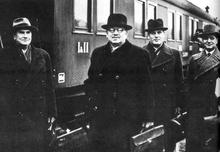 Um grupo de quatro homens usando chapéus e uma cauda atrás.
