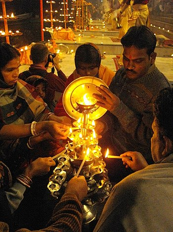English: Multi-tiered aarti stand being lit, d...