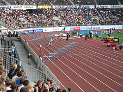 A women's 400 m hurdles race on a typical outdoor red urethane track in the Helsinki Olympic Stadium in Finland.
