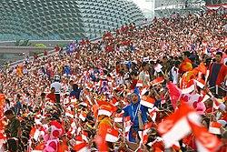 Массовое мероприятие, на котором люди размахивают флагом на стадионе