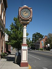 "Street clock and (at right) post office. The legend on the clock says ""Live better electrically."" The post office is listed on the National Register of Historic Places."