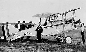 Side view of single-engined biplane surrounded by five men
