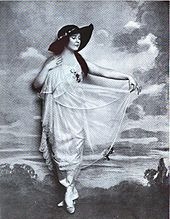 Black and white full-length portrait of a white woman wearing a white dress and a dark hat.