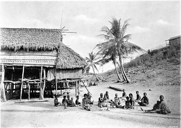 Black and white photograph of people sitting on the ground next to a building, with palm trees in the background.