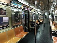 The interior of an R62 car on the 3 train. Its seats are yellow and orange, with several advertisements hanging above.