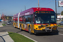 "A red-and-yellow articulated bus seen on a suburban street from a nearby sidewalk. The bus's front sign reads ""[A] Federal Way TC""."