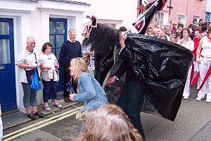 Hobby horse - The Old 'Oss capturing a young woman during the May Day festival at Padstow, Cornwall