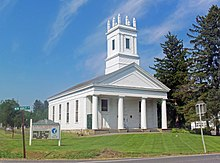 "A white church with a colonnaded front and square steeple topped with spiky finials on the corners on a mowed grassy area under a blue sky. Behind it on the right are tall evergreen trees. In front on the left is a sign saying ""Reformed Church of New Hurley"" and a green street sign with ""New Hurley Road"" on it"