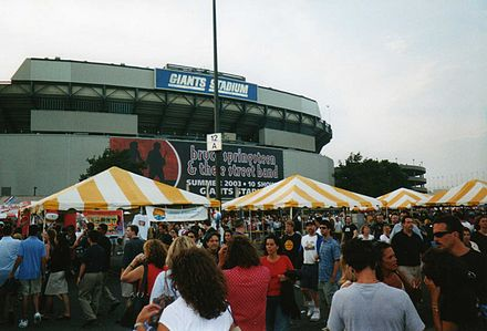 The scene outside the Giants Stadium parking lot for banner-marked, record-setting, 10-night stand of The Rising Tour during July 2003. RisingTourGiantsStadiumLot.jpg