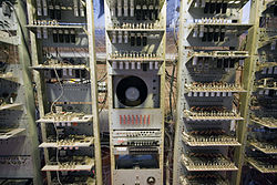 Close-up view of three tall racks containing electronic circuit boards, with a cathode ray tube in the middle of the central rack. Below the CRT is a panel containing four rows of eight switches.