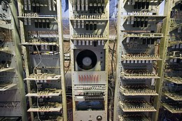 Three tall racks containing electronic circuit boards