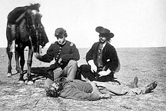 Dodge City, Kansas - Buffalo hunter Ralph Morrison who was killed and scalped December 7, 1868 near Fort Dodge Kansas by Cheyennes: Lt Reade of the 3rd Infantry and Chief of Scouts John O. Austin are in the background. Photograph by William S. Soule.